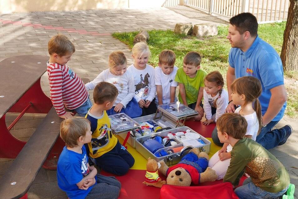 Was kann man für den verletzten Teddy tun? Ralf Rehwagen vermittelt einer Kindergruppe die Grundlagen der Ersten Hilfe.