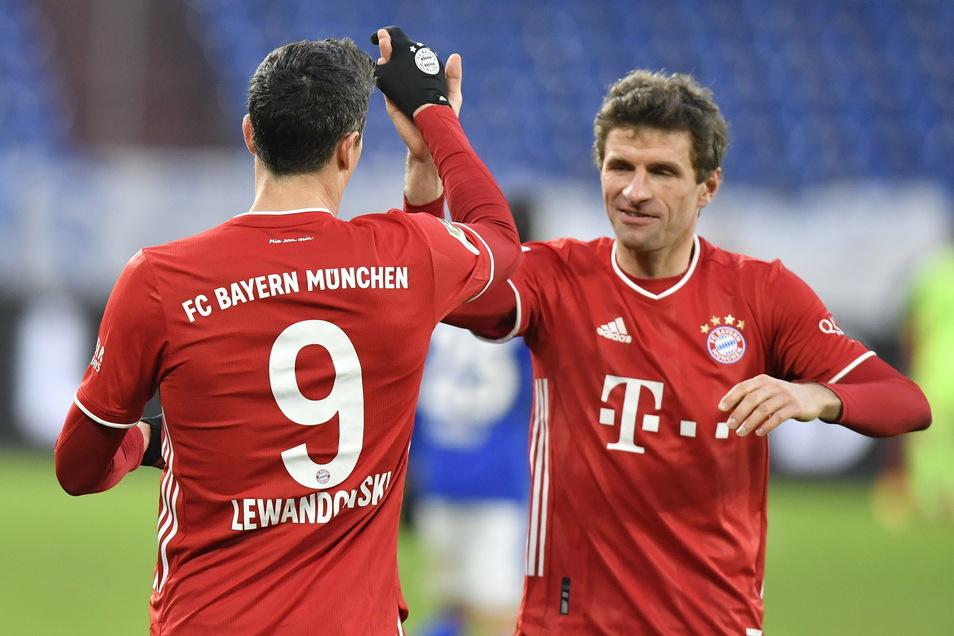 Münchens Robert Lewandowski (l) bejubelt sein Tor zum 0:2 mit Thomas Müller, der gegen Schalke zweimal traf.