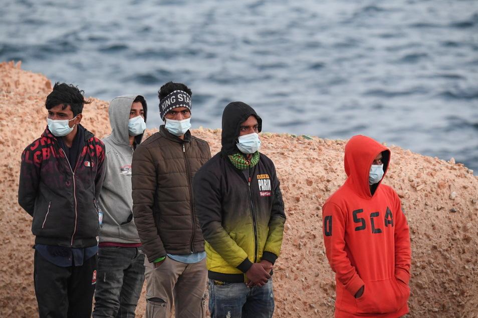 Migranten mit Mund-Nasen-Schutz stehen auf Lampedusa.