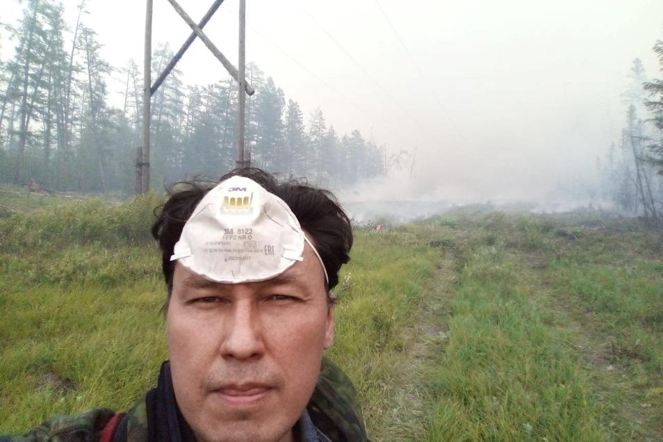 Albert Wassiljew steht in einem Wald in der russischen teilrepublik Jakutien, wo schwere Wald- und Flächenbrände gewütet haben. Der Unternehmer hat sich freiwillig gemeldet, um die Feuerwehren beim Löschen zu unterstützen.
