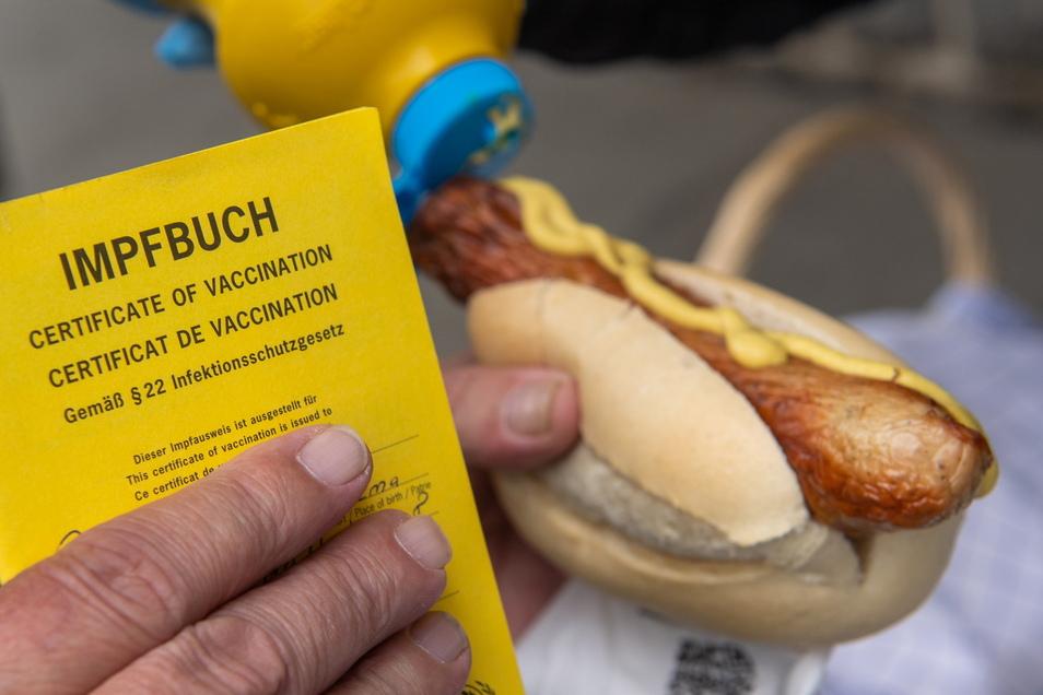 Ein Mann hält am mobilen Impfzentrum in Bad Schlema seinen Impfpass und seinen Belohnungs-Roster.