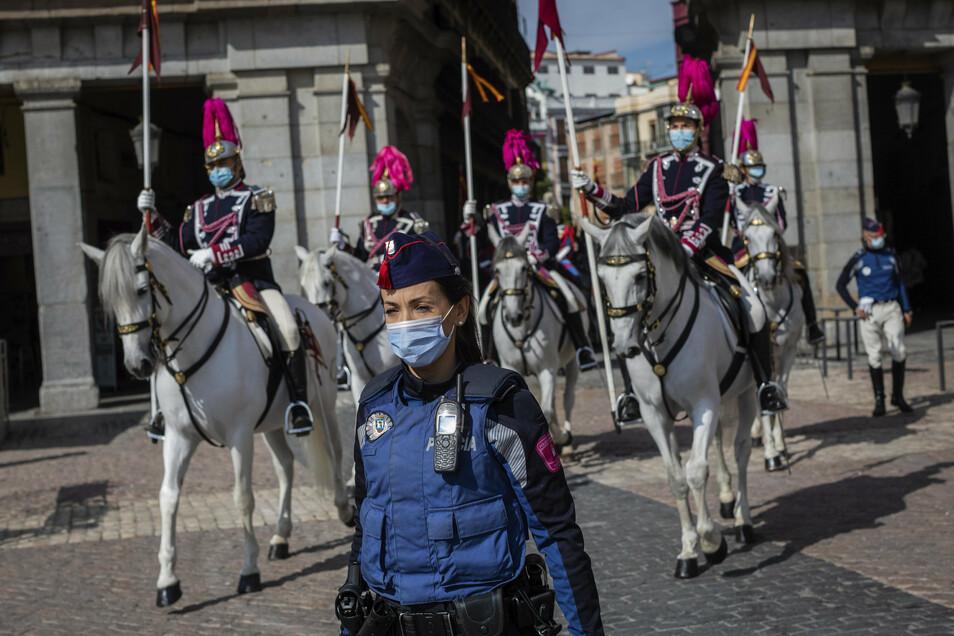 Mitglieder der Königlichen Garde mit Mund-Nasen-Schutz reiten in Richtung Außenministerium in der Innenstadt von Madrid.