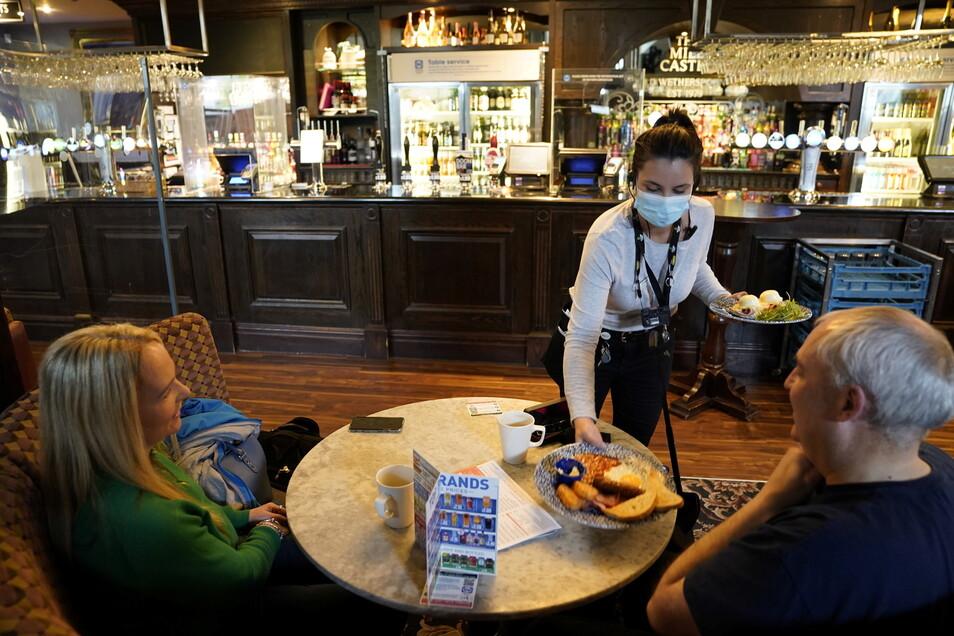 Großbritannien, Newcastle: Eine Kellnerin bringt zwei Gästen im Mile Castle Pub eine Mahlzeit an den Tisch. Die Menschen in weiten Teilen Großbritanniens haben wieder deutlich größere Freiheiten.