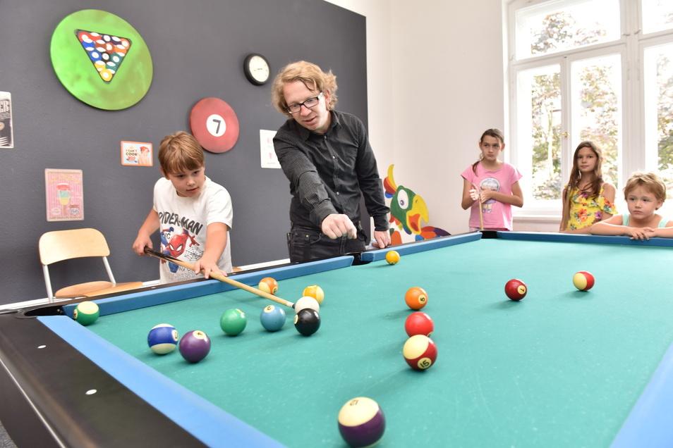 Benjamin Drechsler ist Projektleiter der Hafenkante und weiht die jüngeren Gäste ins Billardspiel ein.