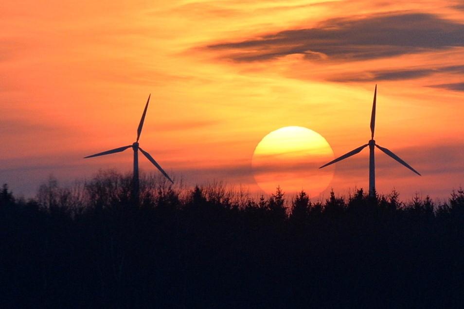 Bei Beerwalde geht die Sonne hinter den Windkraftwerken unter.