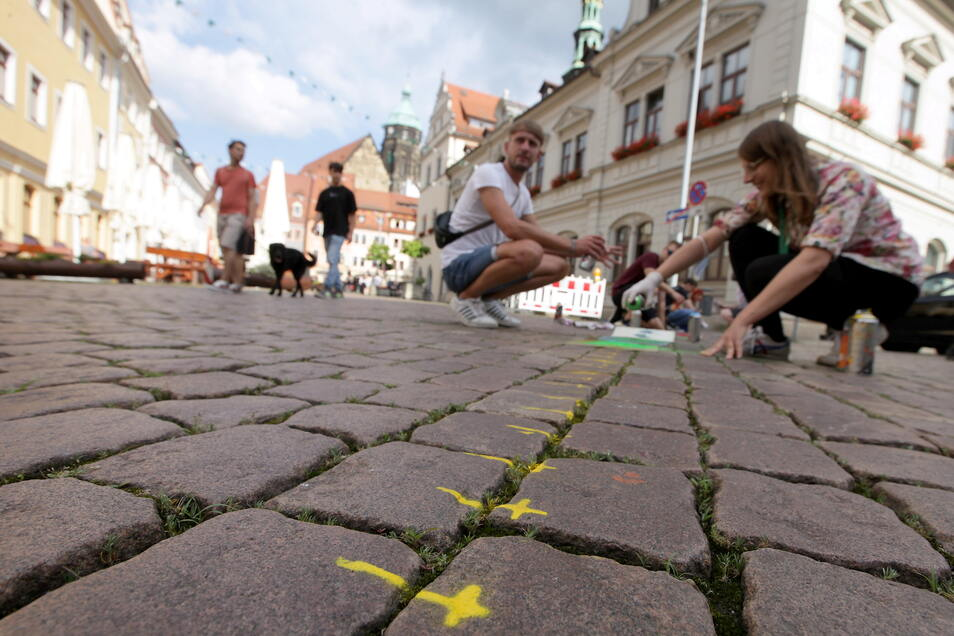 Teilnehmer der CSD-Themenwoche sprühen die Gedenkkreuze auf dem Markt in Pirna nach