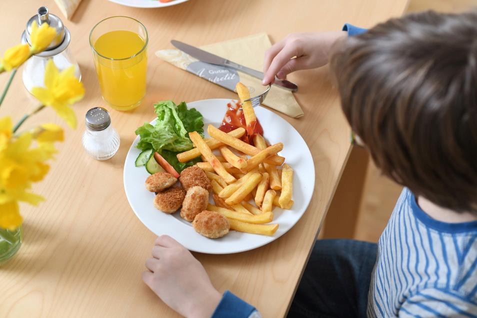 Ein bis zweimal im Monat reicht: Junkfood wie Chicken Nuggets mit Pommes und Ketchup sollten Kinder nur gelegentlich essen.