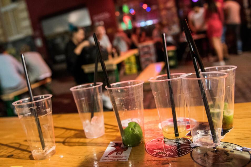 Leere Plastikbecher stehen vor einer Kneipe auf einem Tisch.