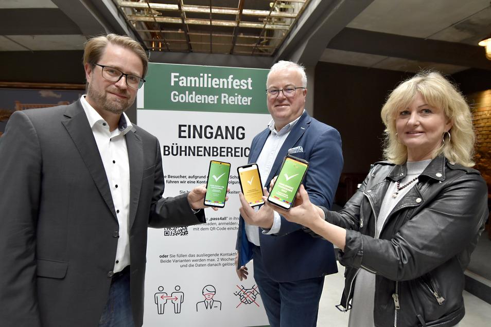 Die Corona-App Pass4all von Jörg Meißner (links) und Kathleen Parma wird beim Familienfest Goldener Reiter ausprobiert. Veranstalter Frank Schröder nutzt die Technik, aber die Namen von Besuchern erfährt höchstens das Gesundheitsamt.