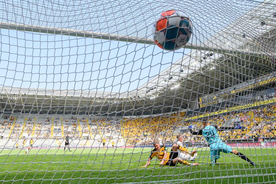Dynamos Christoph Daferner (l) erzielt gegen Ingolstadts Torwart Fabijan Buntic (r) und Maximilian Neuberger das Tor zum 1:0.