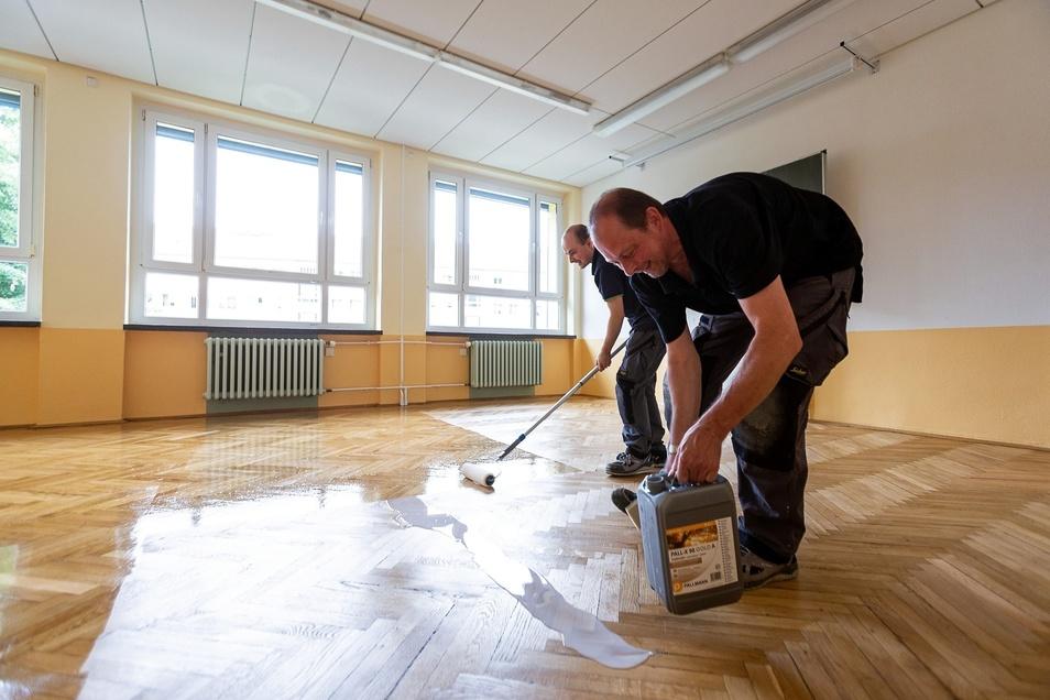 Jörg und Daniel Schirmer von der Firma Schirmer Fußbodenleger versiegeln Parkettböden in der Waldblick-Schule.