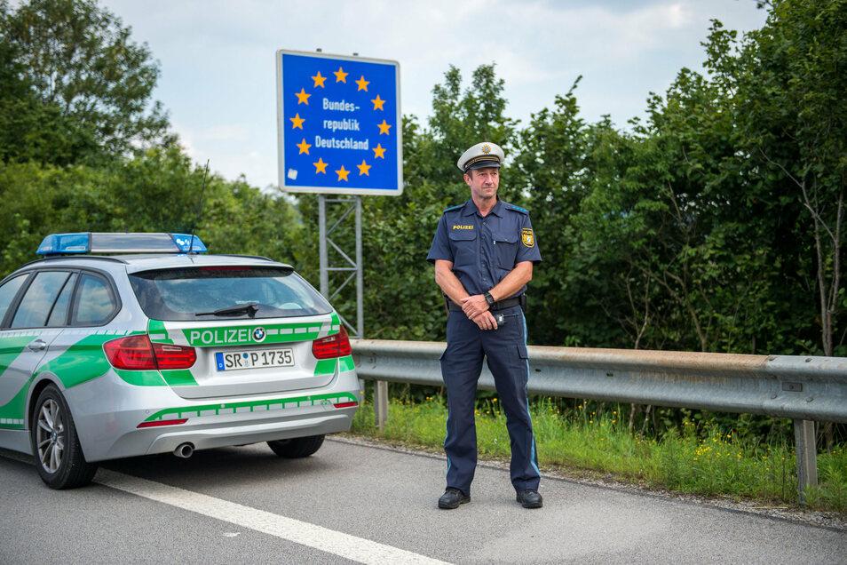 Ein Beamter der bayerischen Grenzpolizei steht am Grenzübergang Kirchdorf an der deutschen Staatsgrenze.