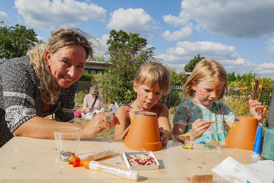 Anja Arlt-Lange vom Großenhainer Team der Outlaw gGmbH bemalte zur Garteneröffnung am Freitag mit Kindern Blumentöpfe – und Nele und Marlene (6) waren mit Feuereifer dabei.