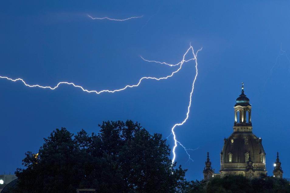 Blitze sind am Himmel neben der Dresdner  Frauenkirche zu sehen.