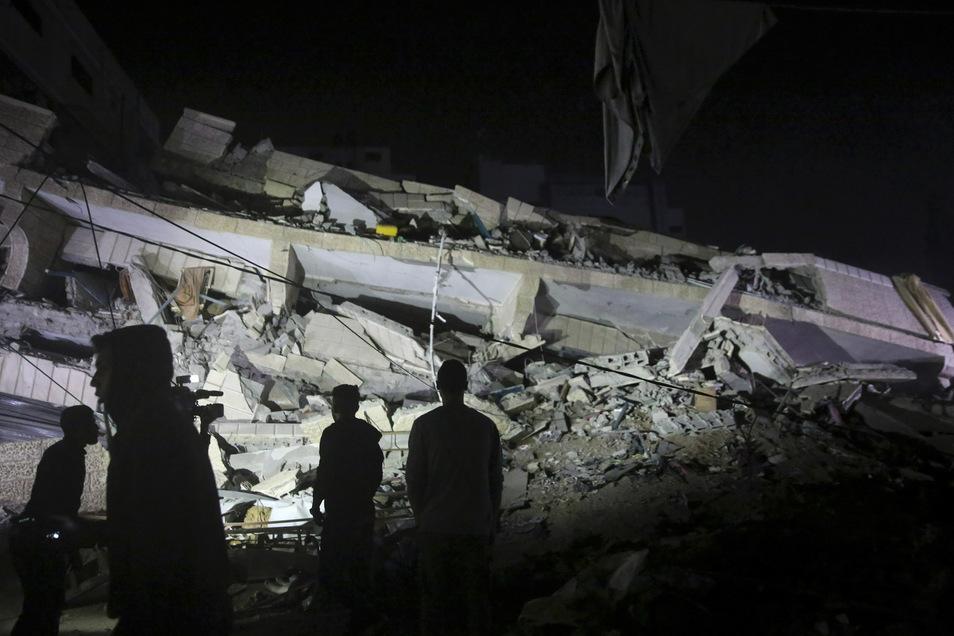 Menschen stehen in Gaza vor einem zerstörten mehrstöckigen Gebäude.