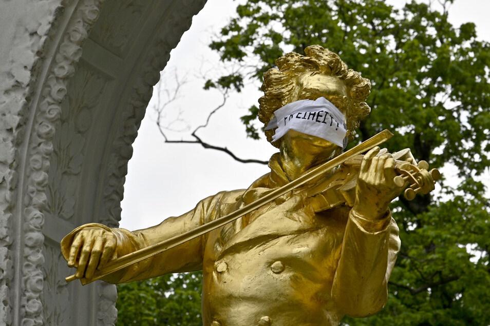 """Die Statue des Johann-Strauß-Denkmals im Wiener Stadtpark trägt einen Mundschutz mit der Aufschrift """"Freiheit!"""""""