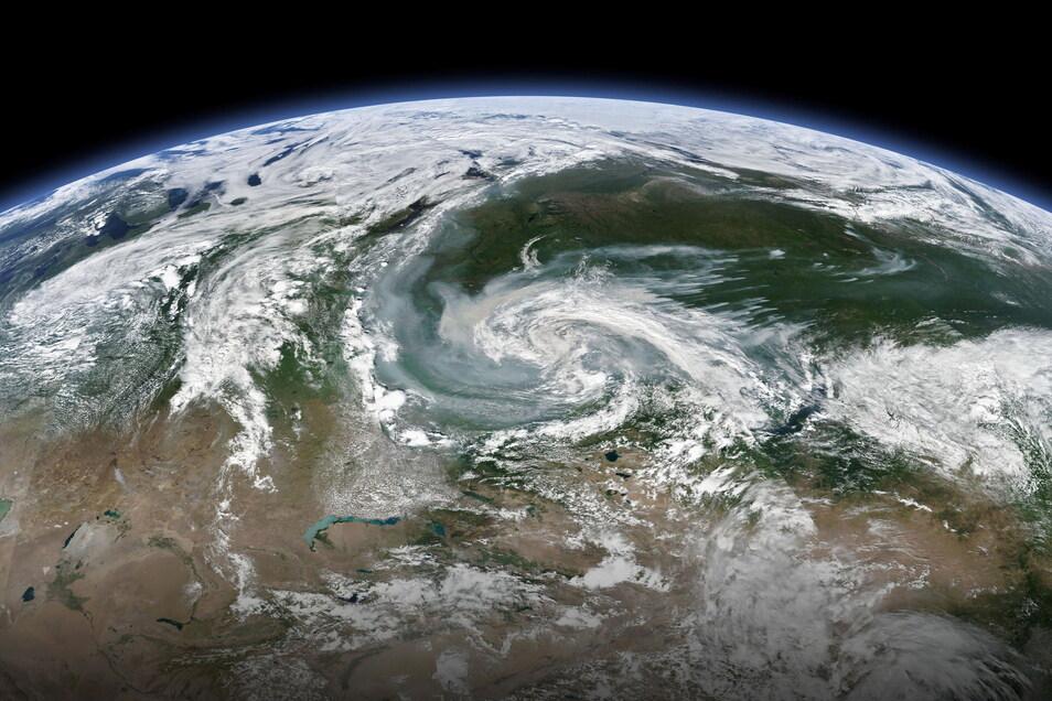 Rauchschwaden, die sich mit einem größeren Sturmsystem vermischen, ziehen über Sibirien.