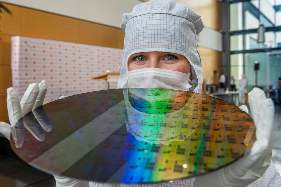 Eine Auszubildende präsentiert einen 300-Millimeter-Wafer in der Chipfabrik von Globalfoundries.
