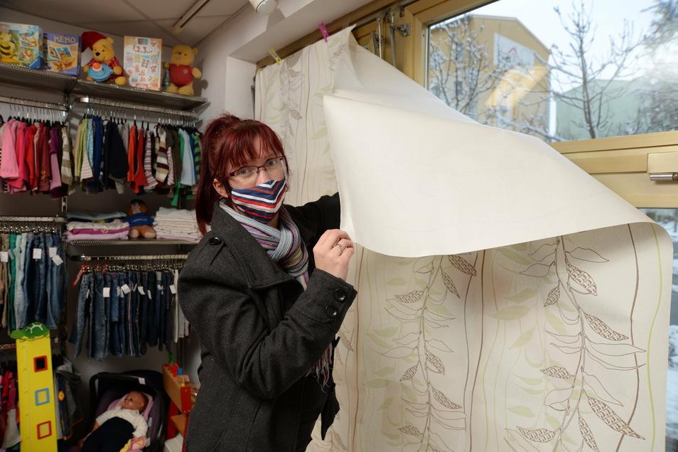"""Ladeninhaberin Corina Friedrich verhüllt das Schaufenster in ihrem Geschäft """"Dreikäsehoch"""". Sie ist die Initiatorin der Händleraktion """"Ohne uns wird es leer in Niesky""""."""