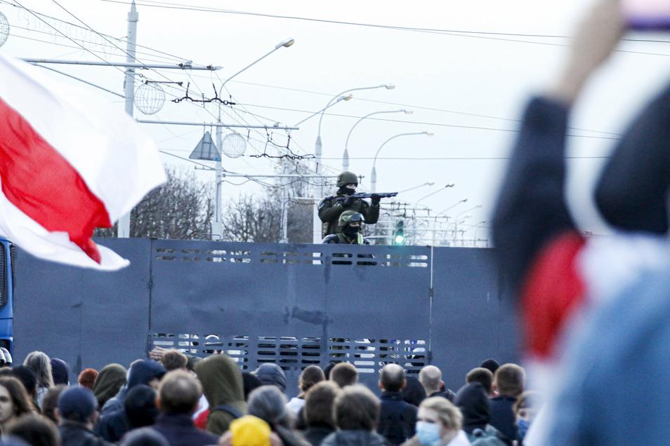 Bewaffnete belarussische Polizeibeamte bewachen während eines Protests in Minsk eine Straßensperre hoch über den Demonstranten.