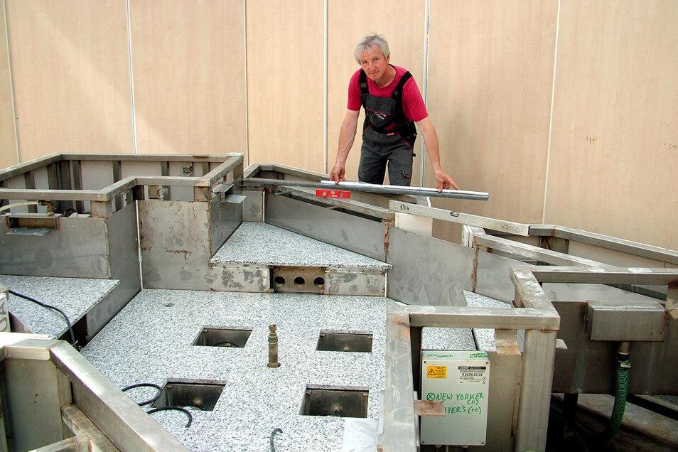 Ronny Klinger ist seit 37 Jahren Fliesenleger – aber er kann weit, weit mehr als eben das. Siehe seine Aufgabe am Lausitz-Center-Brunnen, an dem er hier gerade Maß nimmt für eine Verblend-Leiste.