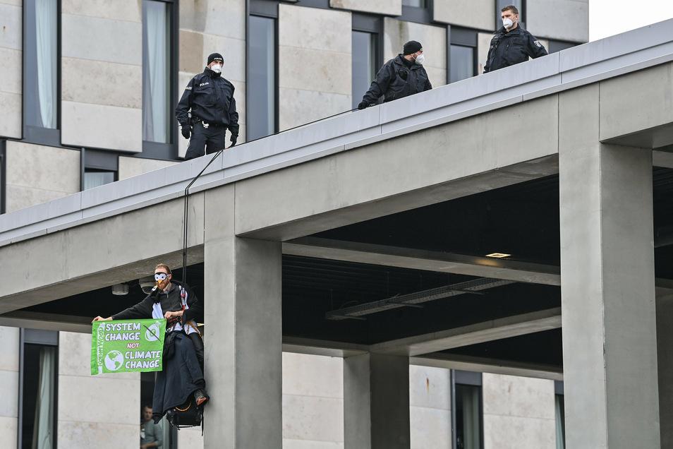 Ein Klima-Aktivist hängt mit einem Transparent an einer Fassade vom Terminal 1.