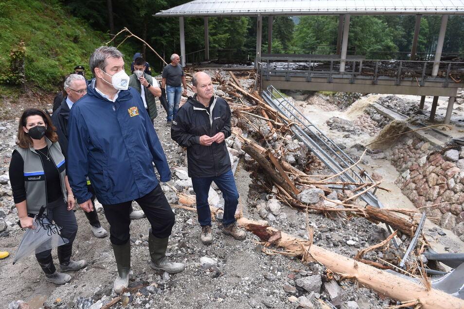 Markus Söder (M, CSU), bayerischer Ministerpräsident, Olaf Scholz (SPD), Bundesfinanzminister, und Michaela Kaniber (CSU), bayerische Landwirtschaftsministerin, stehen bei der durch Unwetter zerstörten Bob- und Rodelbahn am Königssee.