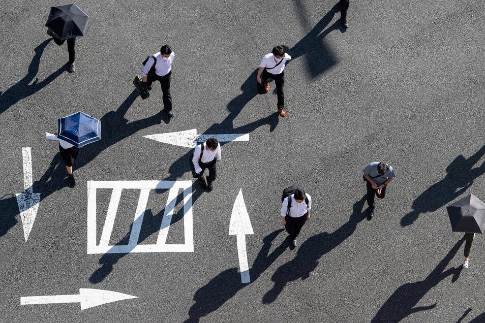 Passanten auf einer Kreuzung in Tokio - die Corona-Infektionen nehmen zu.