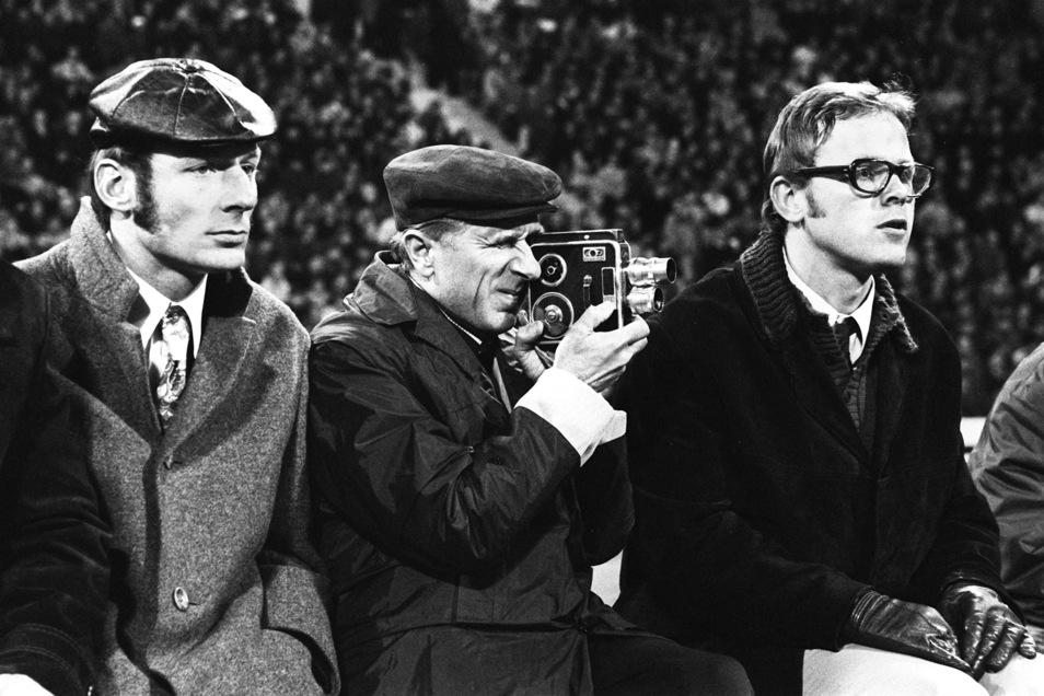 Seine Schmalfilmkamera hatte Walter Fritzsch (M.) immer dabei, filmte selbst während der Spiele von Dynamo. wie hier im Münchner Olympiastadion beim 3:4 gegen die Bayern 1973. An seiner Seite Assistent Gerhard Prautzsch (l.) und Mannschaftsarzt Dr. Wolfga