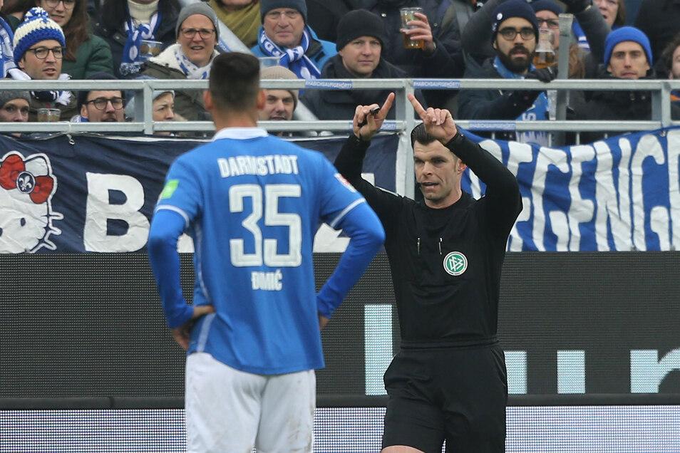 Alexander Sather aus Grimma zeigt Darmstadts Ex-Dynamo Dario Dumic den Einsatz des Videobeweises im Zweitligaspiel gegen Regensburg an, analysiert die strittige Szene und entscheidet auf Foulelfmeter.