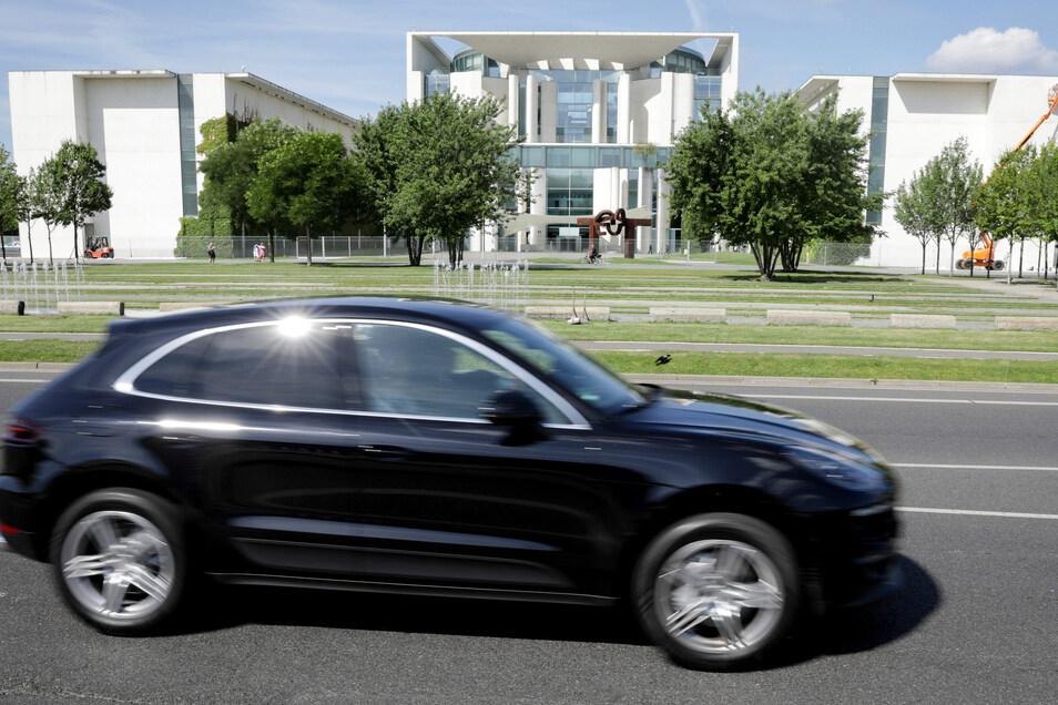 Ein Porsche Macan fährt am Bundeskanzleramt vorbei. Viel Sprit verbrauchende Autos werden über die Kfz-Steuer ab 2021 etwas teurer.