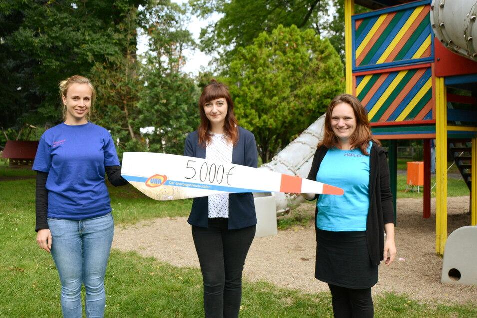 UKA-Pressesprecherin Lisa Fritsche (Mitte) übergibt den symbolischen Spendenscheck in Form des Rotorblatts einer Windenergieanlage an Marlen Linke (rechts) und Karla Rohde vom Flexiblen Jugendmanagement Meißen.