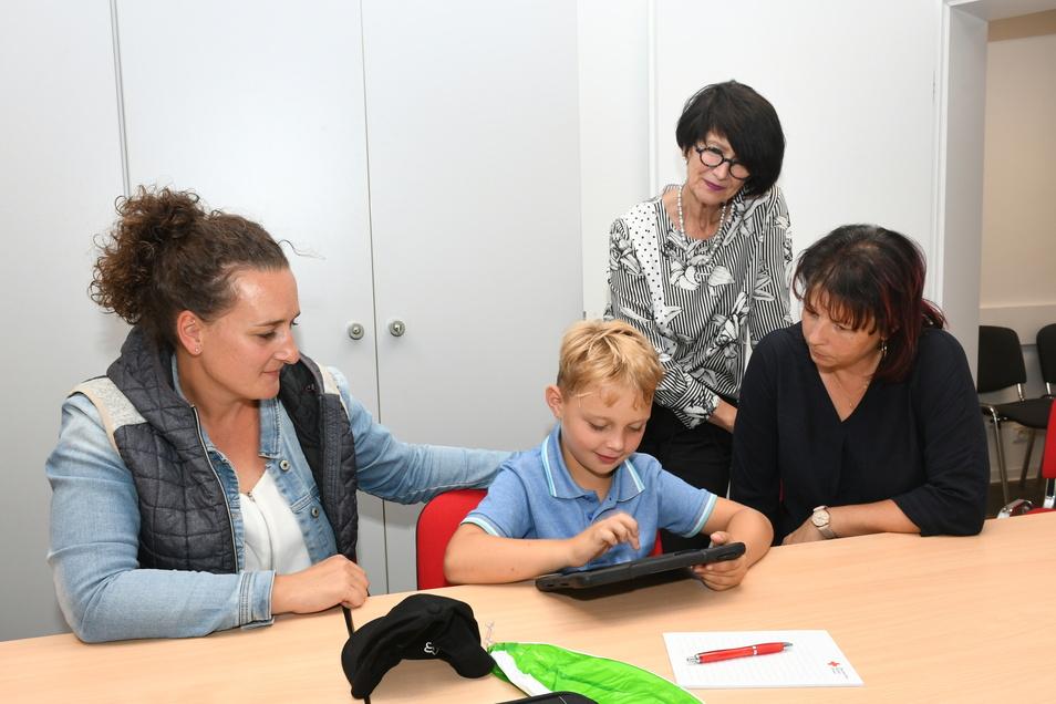 Der sechsjährige Nilo Elsner kommt schon gut zurecht auf dem Tablet. Mutti Anne Elsner, Sabine Brumma und Heike Marko schauen ihm während der ersten Stunde zur Einführung in die Arbeit mit dem Tablet über die Schulter.