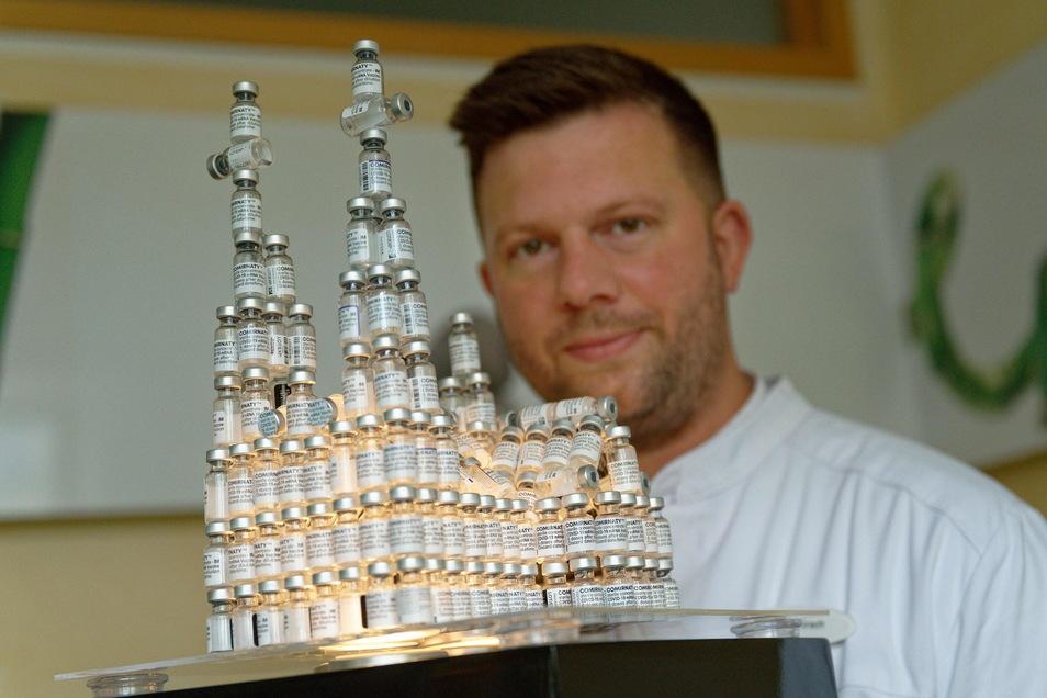 Der Kölner Arzt Bastian Kirsch neben seinem Dom-Modell aus leeren Impfflaschen