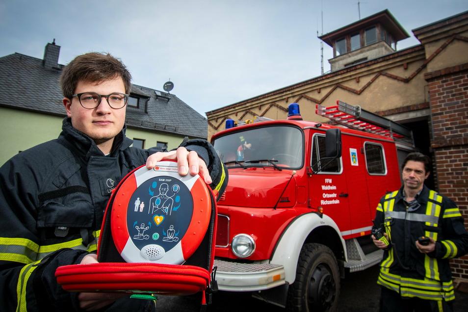 Gruppenführer Nick Ziegenbalg (vorn) und der stellvertretende Ortswehrleiter Andreas Tesch von der Ortswehr Richzenhain freuen sich über den Defibrillator. Das Gerät hat die Björn-Steiger-Stiftung zur Verfügung gestellt.