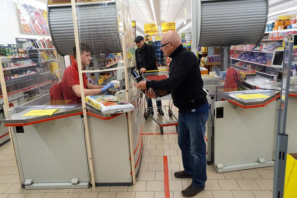 Kassierer Tom Schweigler aus Wehlen arbeitet hinter einer durchsichtigen Plastikfolie im Kassenbereich, auf dem Boden sind Markierung für den Abstand der Kunden aufgeklebt, Werner Linnè aus Copitz (mit Brille) hat gerade ú.a. Blumenerde eingekauft;
