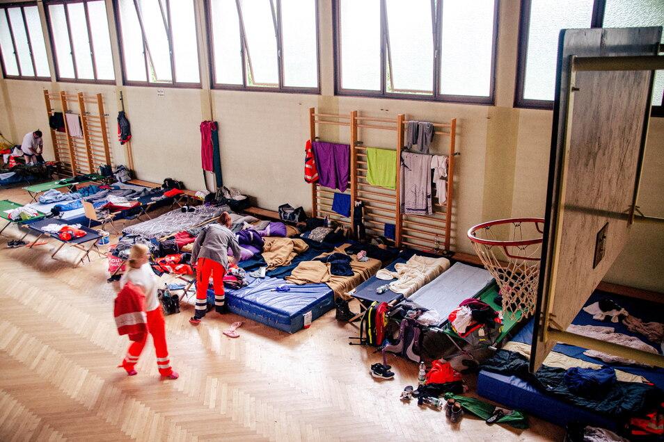 """Ein Notlager in einer Turnhalle. Ein mal zwei Meter Feldbett, die manche Menschen jetzt """"Zuhause"""" nennen müssen."""