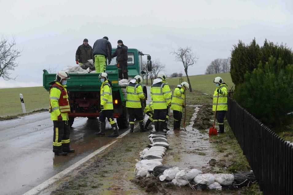 Die Kameraden der Oderwitzer Feuerwehr haben an der Spitzbergstraße Sandsäcke gestapelt, weil Wasser von den Feldern auf die Straße floss.