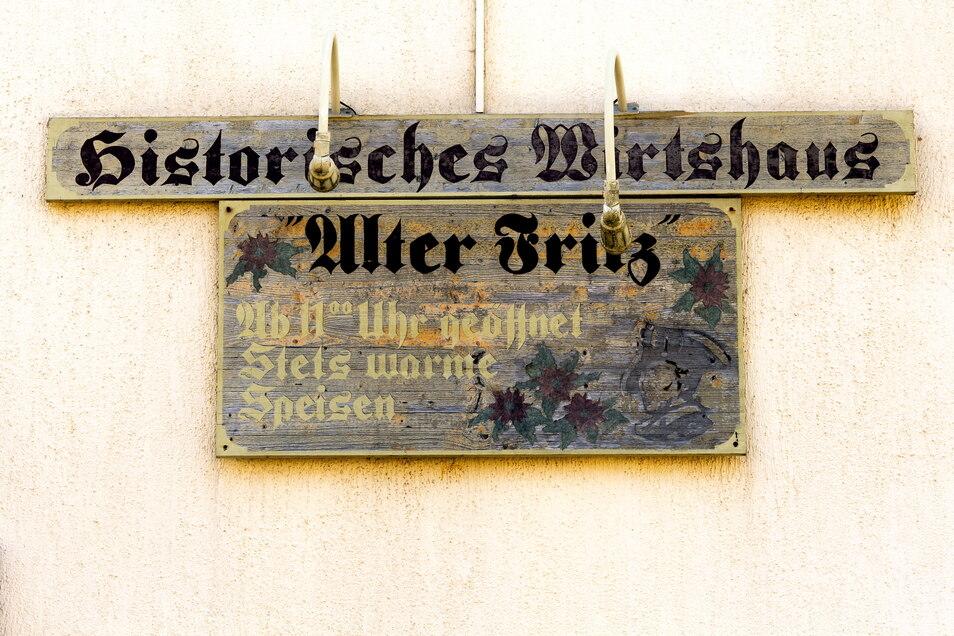 """Ein Schild aus besseren Tagen hängt noch heute an der Rückseite des Gasthauses """"Alter Fritz"""". Daneben sind Kanonenkugeln in die Fassade eingemauert. Sie stammen aus der Schlacht bei Hochkirch im Jahr 1758."""