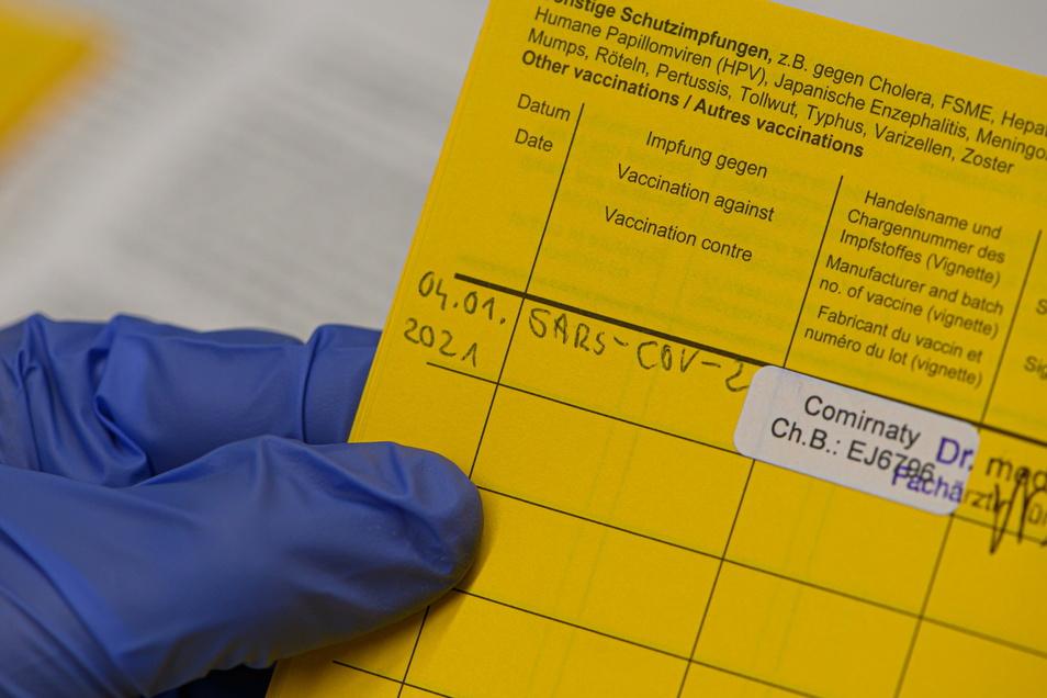 Eine Mitarbeiterin im Städtischen Klinikum Dresden trägt in einem Impfausweis die Impfung gegen Corona ein. In Deutschland haben Geimpfte bisher keinen Vorteil gegenüber Ungeimpften.