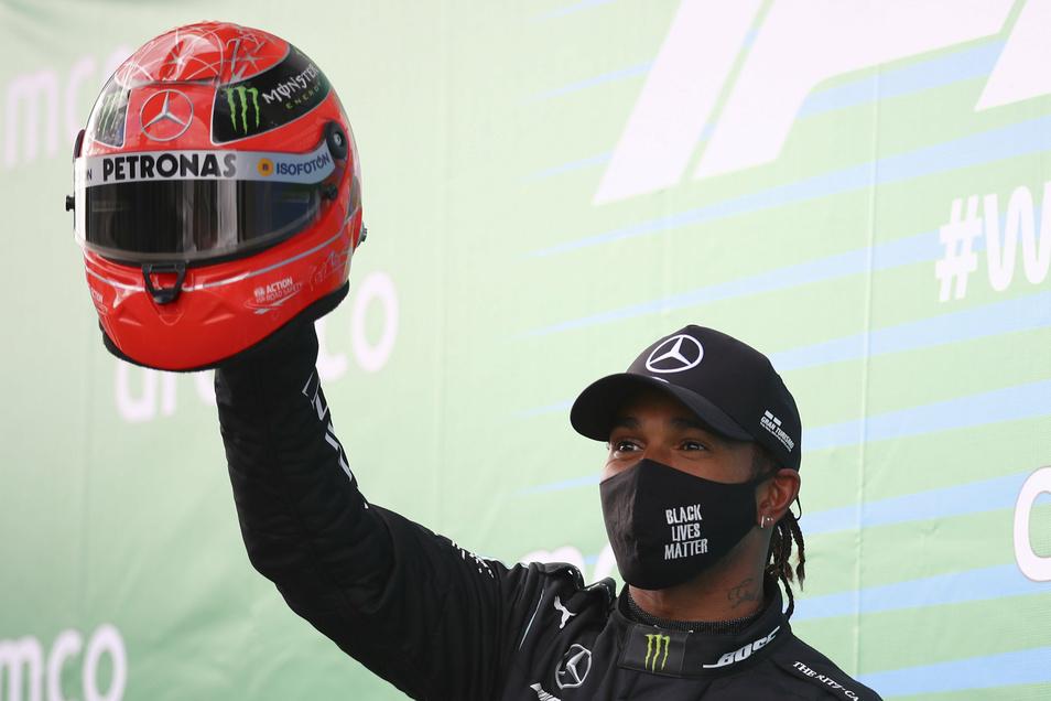 Lewis Hamilton hält nach seinem Erfolg beim Großen Preis der Eifel auf dem Nürburgring einen Helm von Michael Schumacher hoch.