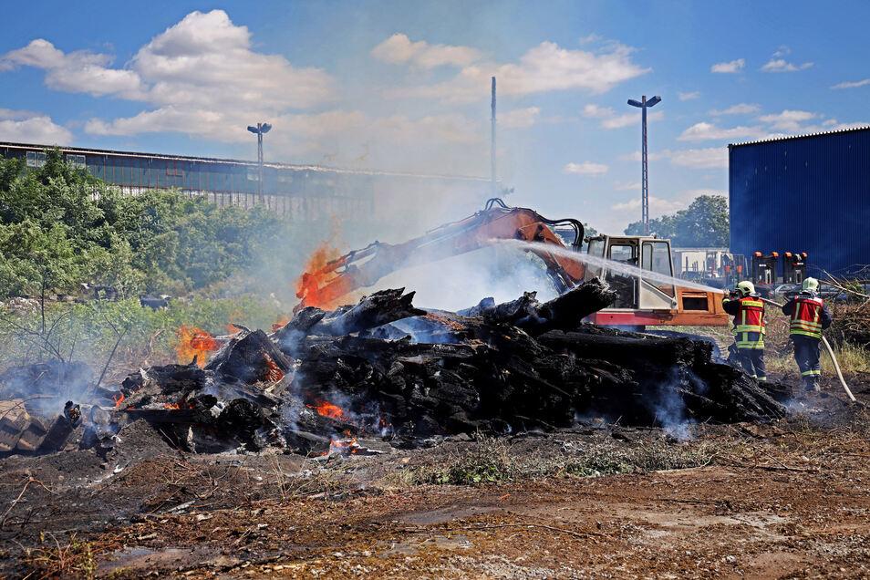 Riesaer Feuerwehrleute löschen diesen brennenden Holzhaufen auf dem Gelände der Firma Brand.