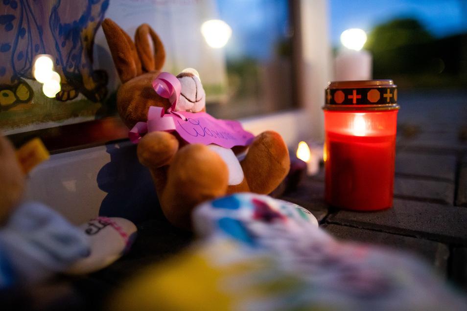 Stofftiere und Kerzen liegen vor dem Eingang der Kindertagesstätte.