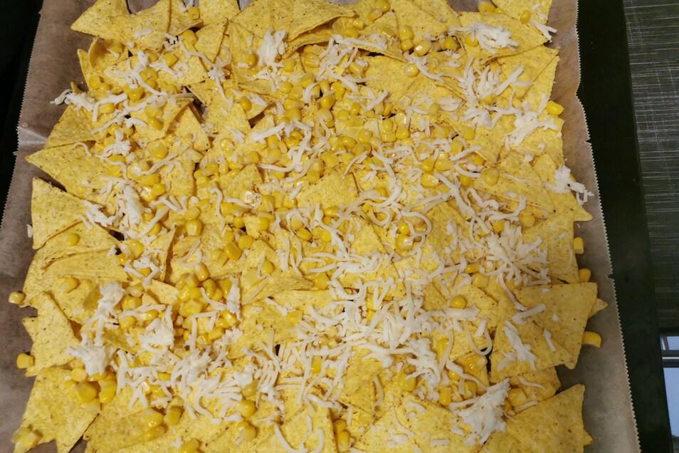 5. Schritt: Mais abtropfen lassen. Nachos auf einem Backblech (mit Backpapier bzw. Backunterlage) verteilen. Den Mais darüber und mit Käse bestreuen.