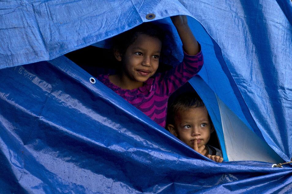 Migranten schützen sich in einem provisorischen Zelt vor dem Regen an der mexikanischen Grenze zu den USA.