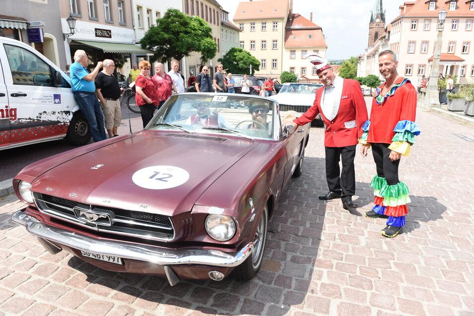 Mitglieder des Leisniger Carneval Clubs begrüßen Robert Athner und Toni Josteid, Teilnehmer der CC-Rallye Sachsen mit ihrem Ford in Leisnig und übergeben ein kleines Geschenk.