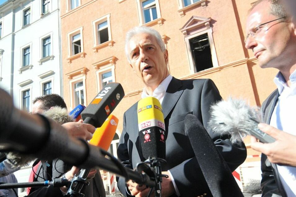 Vor der Brandstätte erklärt Ministerpräsident Stanislaw Tillich das Thema abermals zur Chefsache und lässt seinen Innenminister Markus Ulbig gut zuhören.