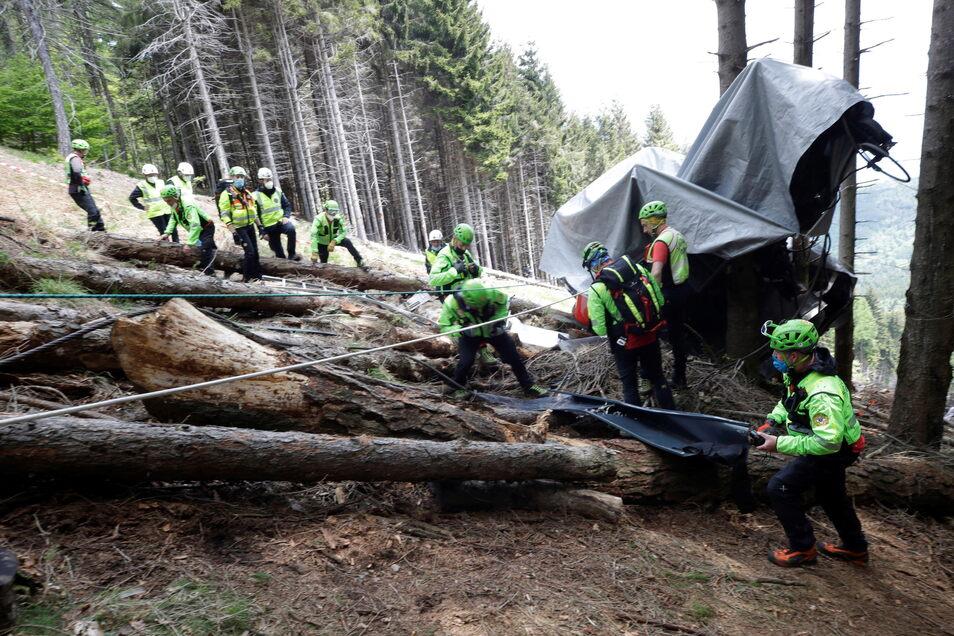 Rettungshelfer untersuchen die Trümmer der Seilbahngondel.