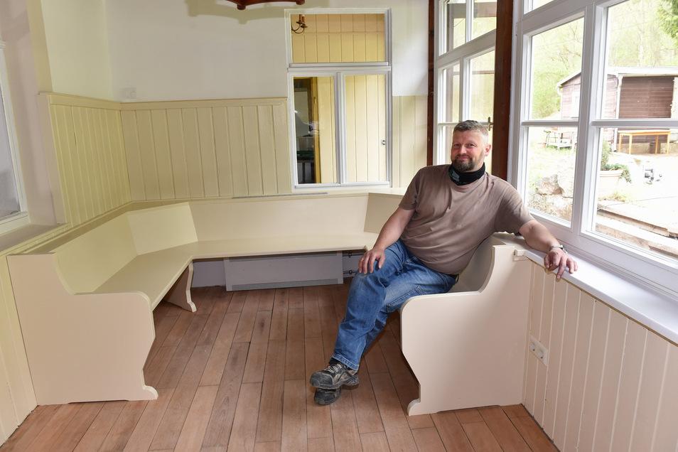 Dirk Hahmann sitzt auf einer neu gebauten Bank im früheren Eingangsbereich der Veranda.