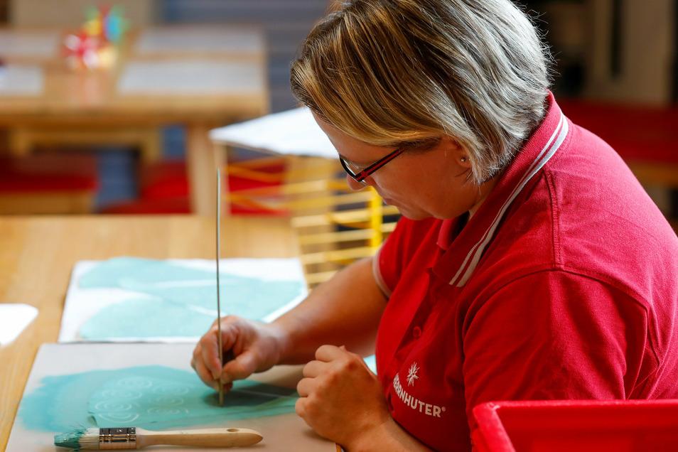 """Jana Heinze """"malt"""" mit einem Holzstäbchen Schneckenschnirkel in die feuchte Farbe."""